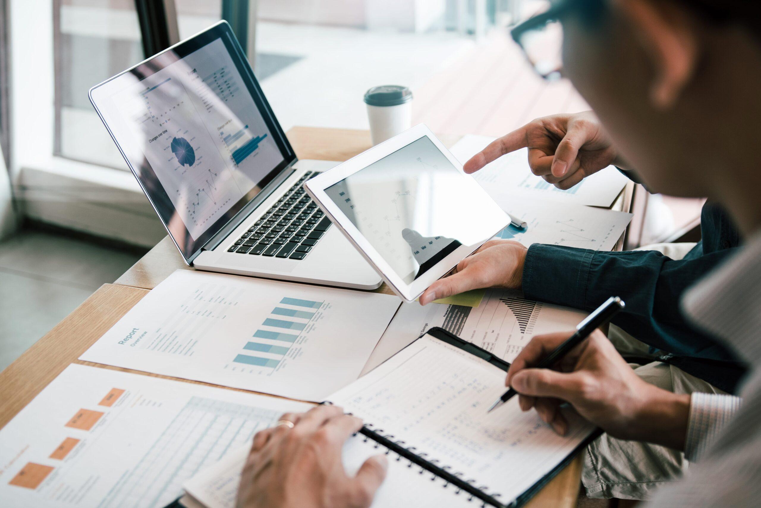Pessoas analisando dados sobre a empresa em tablet, computador e papéis.