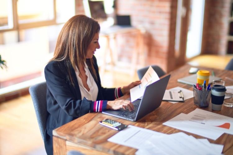 Mulher olhando para documentos e mexendo no computador.