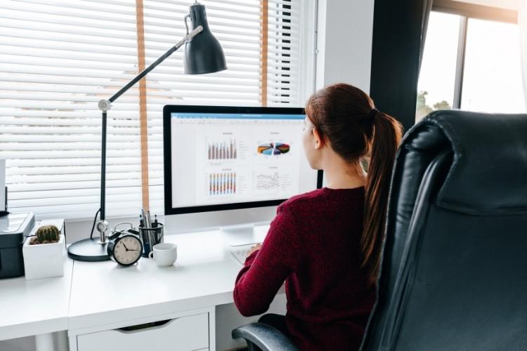 Mulher analisando gráficos em computador.