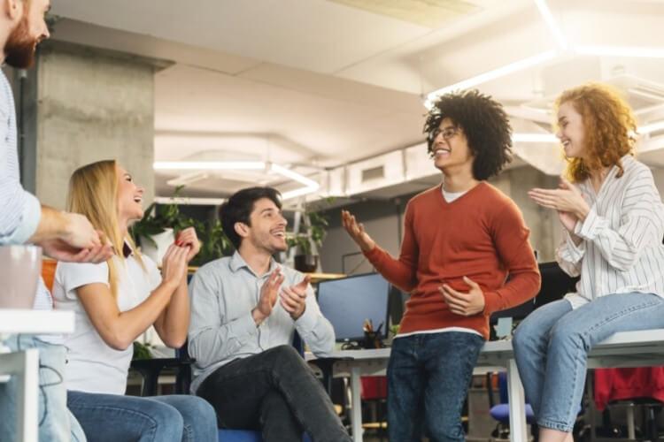 Equipe de trabalho diversa reunida, sorrindo e conversando.