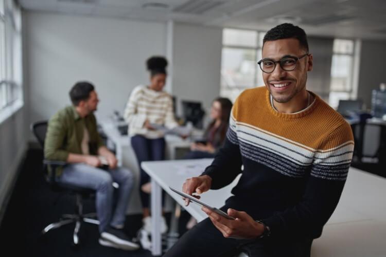 Homem de suéter sentado em cima da mesa, com tablet na mão, sorrindo.