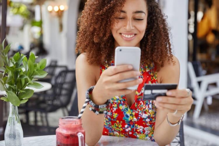 Mulher fazendo compra com cartão de crédito, aproveitando cupom de desconto.