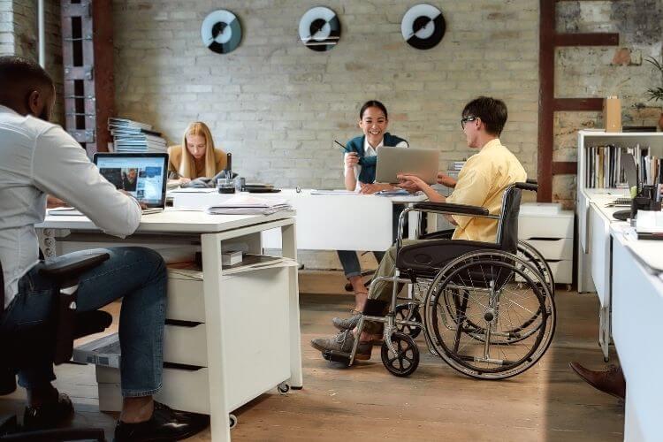 Cadeirante, homem negro e mulher convivendo em um ambiente de trabalho agradável.