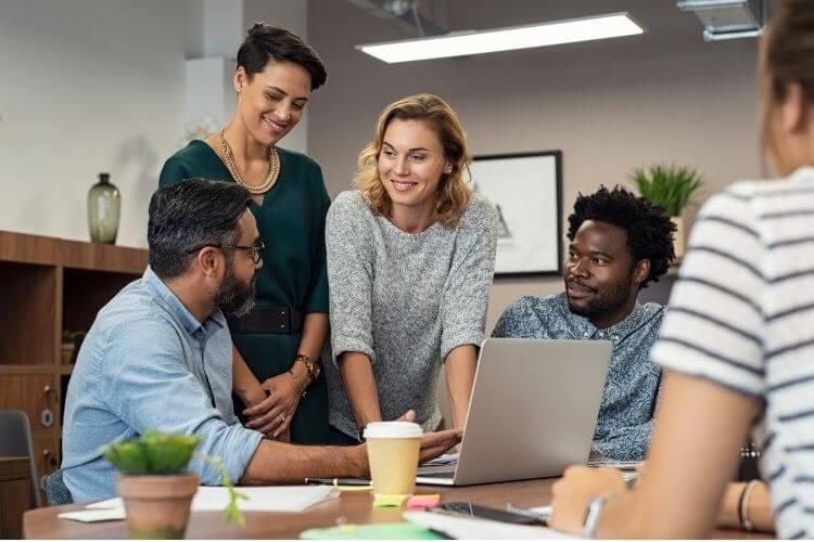 Equipe de trabalho diversa reunida no computador para construir EVP.