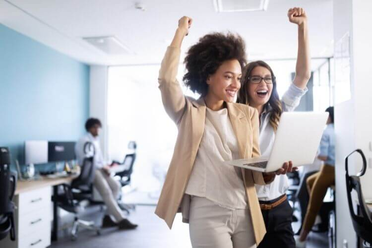 Mulheres de negócios com as mãos para cima, sorrindo e comemorando.
