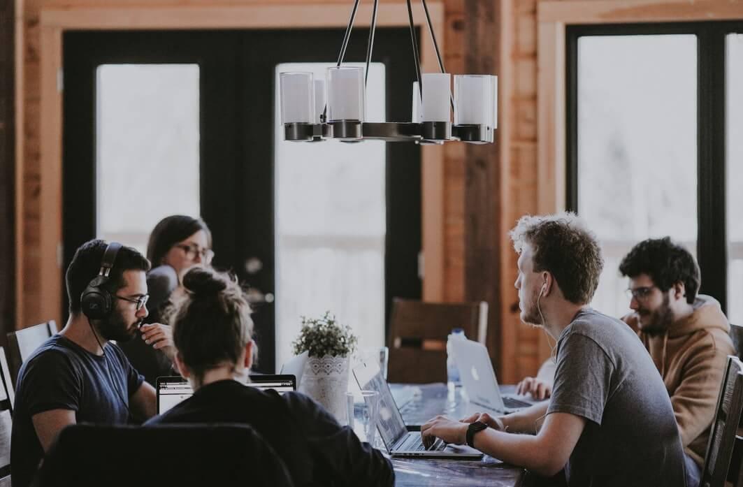 Equipe de trabalho ao redor de uma mesa, conversando.