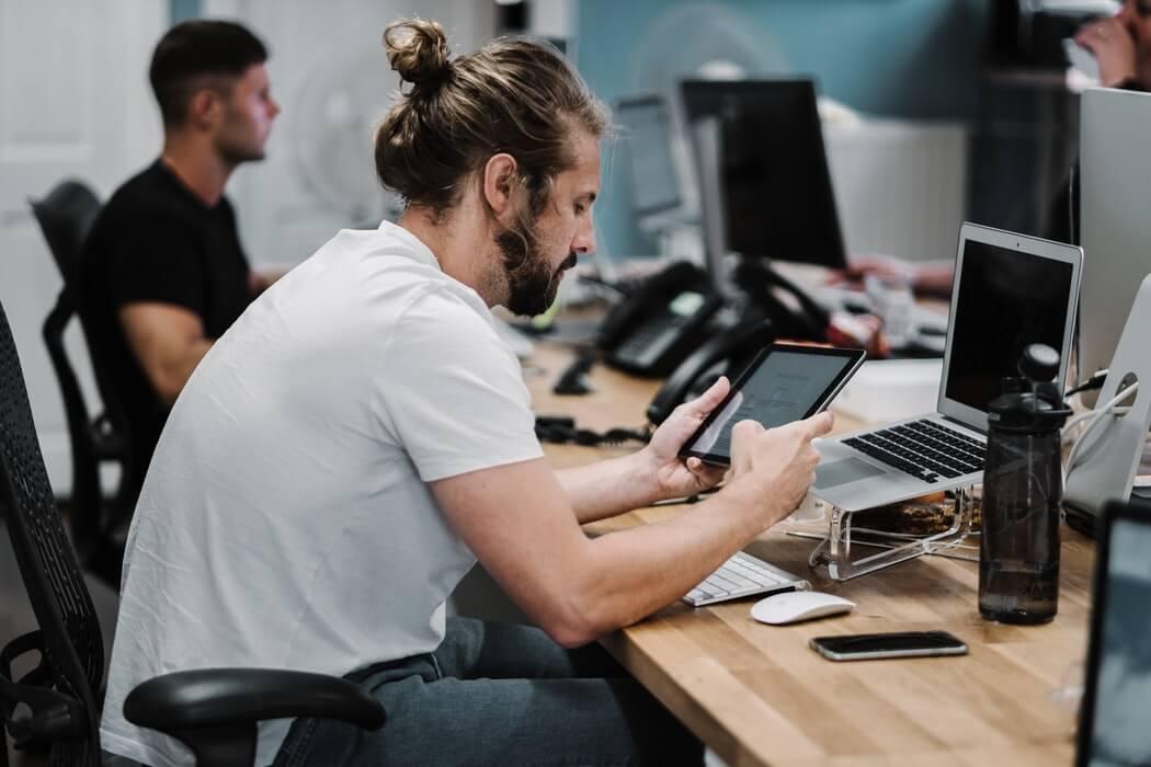 Homem sentado à mesa de trabalho, mexendo em um tablet.