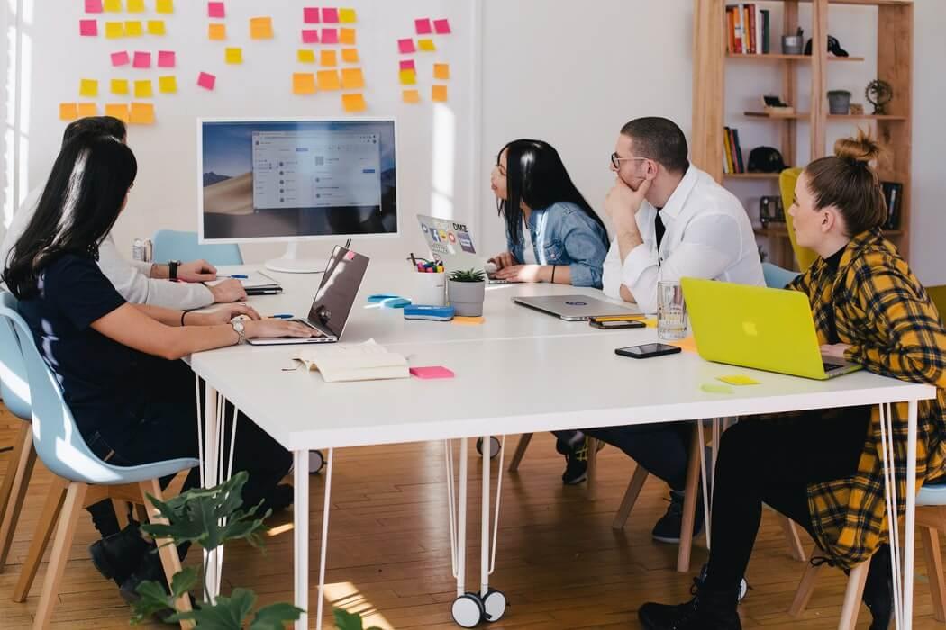 Time ao redor de uma mesa, em frente a uma parede de post its, traçando estratégias.