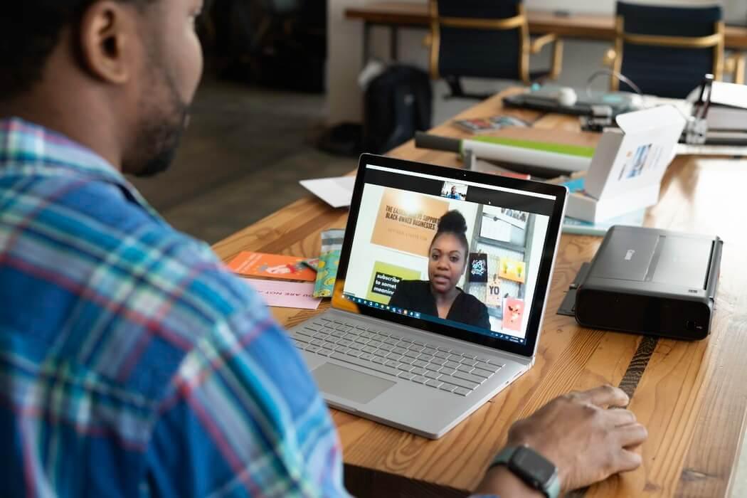 Homem negro fazendo curso com professora mulher pelo computador.