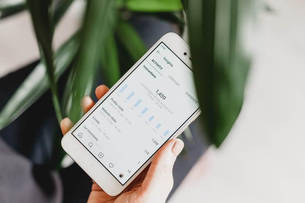 Celular com dados das redes sociais na tela.