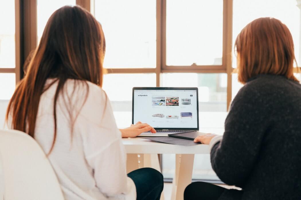 Dupla de mulheres mexendo em um programa de tecnologia do RH.
